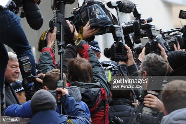 Members of the press take images of Vatican finance chief Cardinal George Pell as he leaves after a hearing at the Melbourne Magistrates Court in...