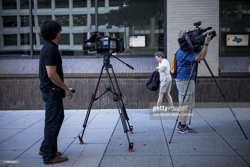 Members of the press wait outside The Washington Post August 5, 2013 in Washington, DC after it was announced that Amazon.com founder and CEO Jeff Bezos had agreed to purchase the Post for USD 250 million. Multi-billionaire Bezos, who created Amazon, which has soared in a few years to a dominant position in online retailing, said he was buying the Post in his personal capacity and hoped to shepherd it through the evolution away from traditional newsprint. AFP PHOTO/Brendan SMIALOWSKI