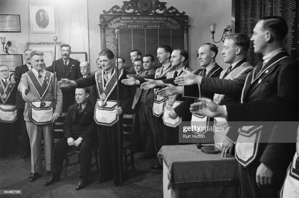 Members of the 'Pride of Clapham' lodge of the Manchester Unity of Odd Fellows an independent friendly society toast a new member after his election...