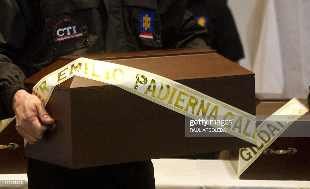 A members of the Prosecutor's Office carries the urn with the remains of a person disappeared during the Colombian civil war, on June 21, 2013 in Medellin, Antioquia department, Colombia. In a ceremony, relatives of 36 victims received the remains of their loved ones, which were recently found in common graves due to information given by demobilized combatants of both, leftist guerrillas and right-wing paramilitary groups, in the framework of the country's peace process. AFP PHOTO/Raul ARBOLEDA