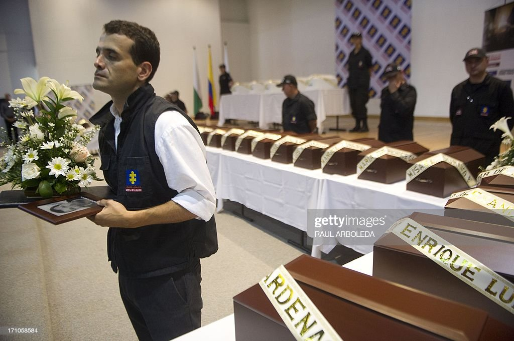 A members of the Prosecutor's Office holds the urn with the remains of a person disappeared during the Colombian civil war, on June 21, 2013 in Medellin, Antioquia department, Colombia. In a ceremony, relatives of 36 victims received the remains of their loved ones, which were recently found in common graves due to information given by demobilized combatants of both, leftist guerrillas and right-wing paramilitary groups, in the framework of the country's peace process. AFP PHOTO/Raul ARBOLEDA