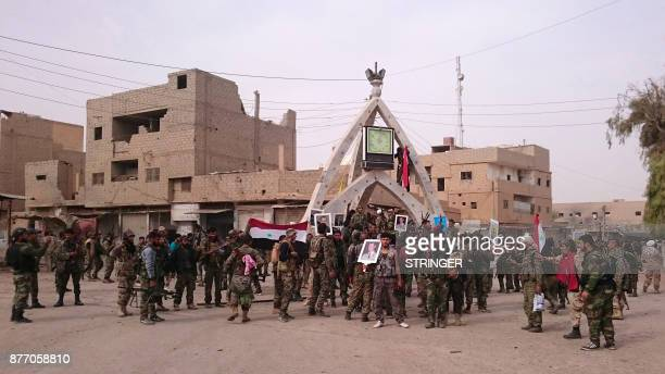 Members of the proSyrian government forces pose with portraits of Syrian President Bashar alAssad and his late father Hafez alAssad as they gather in...