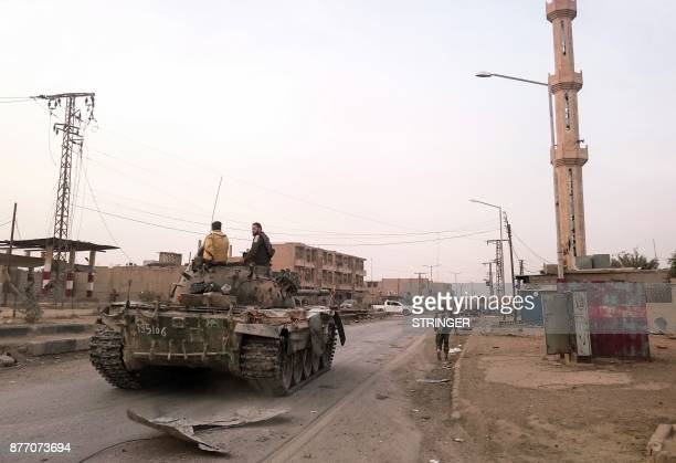 Members of the proSyrian government forces ride on a tank as it drives down a street in the Syrian border town of Albu Kamal on November 20 2017...