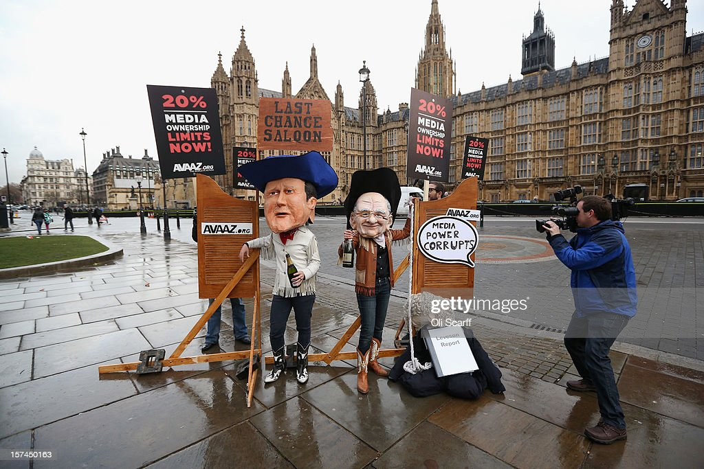 Members of the protest group 'Avaaz' - dressed as cowboy caricatures of David Cameron and Rupert Murdoch - campaign outside the Houses of Parliament for the Government to implement legislation following the Leveson report on December 3, 2012 in London, England. The activists are calling for a 20% limit on the percentage of the media one individual can own.