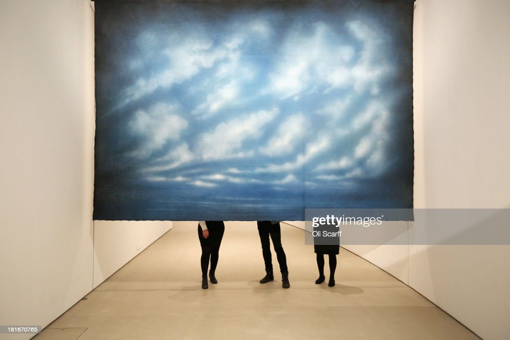 Members of the public admire an installation artwork by Ayse Erkmen entitled 'Intervals' in The Curve art space in the Barbican Centre on September 23, 2013 in London, England. The work consists of 11 large theatrical backdrops which periodically move up and down on an automated system, partitioning the 90 metre long space.