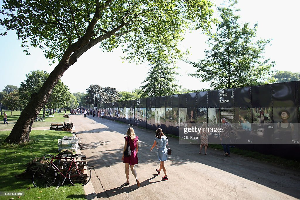 Members of the public admire the photography exhibition 'The World in London' in Victoria Park on July 25, 2012 in London, England. The project, initiated by The Photographers' Gallery, aimed to commission portraits of 204 Londoners, each originating from one of the nations competing in the London 2012 Olympic Games. The project has taken three years to come to fruition and the Photographers' Gallery is still seeking to find sitters from six nations to complete the full set, namely: American Samoa, FS Micronesia, Guam, Marshall Islands, Nauru and Palau.