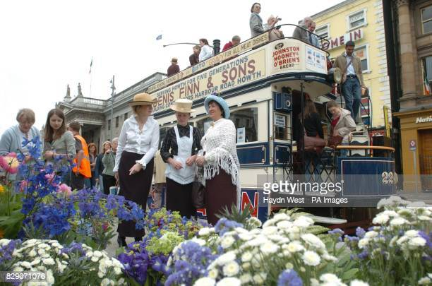 Members of the public and actors dressed in Edwardian costume browse a flower stall beside a parked tram to celebrate the centenary of Bloomsday the...