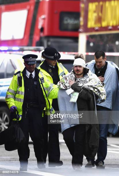 Members of the public are helped by emergency services near Westminster Bridge and the Houses of Parliament on March 22 2017 in London England A...
