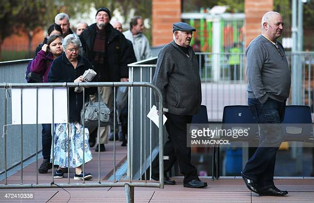 Members of the public arrive to vote at a polling station in Glasgow Scotland on May 7 as Britain holds a general election Polls opened Thursday in...