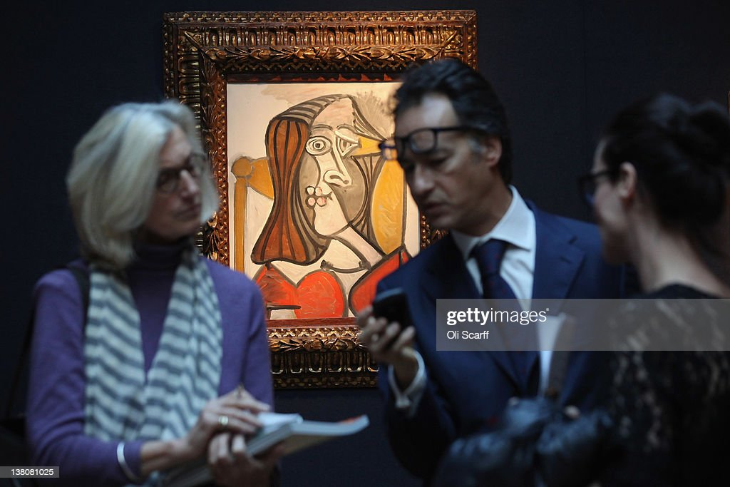Members of the public at Christie's auction house admires a painting by Pablo Picasso entitled 'Femme au fauteuil' on February 2, 2012 in London, England. The artwork, which is estimated to fetch 6 million GBP, is being auctioned in Christie's forthcoming sale 'Living with Art' which will take place on February 9, 2012 and February 10, 2012.