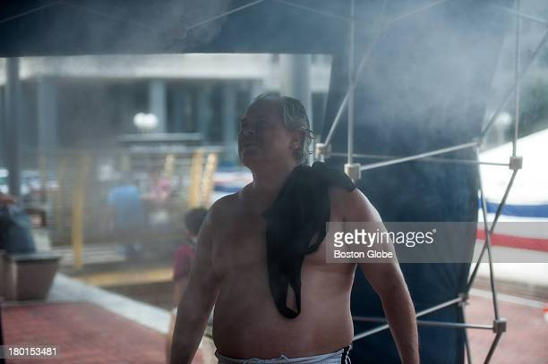 Members of the public cooled off at a vapor shower during another day of 90 degree heat in Boston