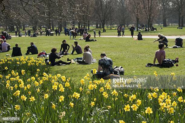 Members of the public enjoy the afternoon sunshine in Green park on April 7 2015 in London England AFP PHOTO/ NIKLAS HALLE'N