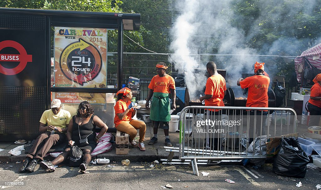 Members of the public enjoying some street food on the first day of the Notting Hill Carnival in west London on August 25, 2013. Running over two days, the Caribbean carnival puts on a Kid's day on the Sunday when costume prizes are awarded and a 'main parade' day on the Monday.