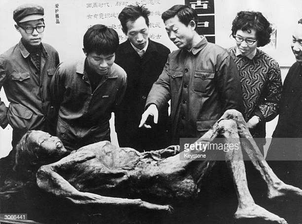 Members of the public examining a three thousand year old mummified corpse in Shanghai
