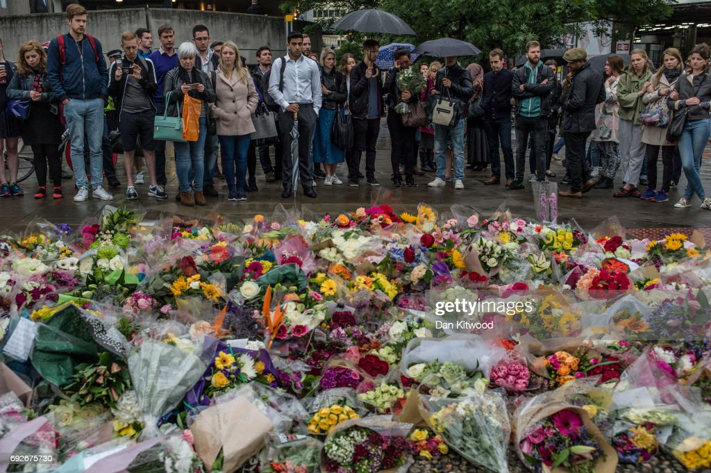 Members of the public gather near flowers on the South side of London Bridge, close to Borough Market in London in tribute to the victims of the June 3 attacks, on June 5, 2017 in London, England. British police on Monday made several arrests in two dawn raids following the June 3 London attacks, claimed by the Islamic State group which left seven people dead.