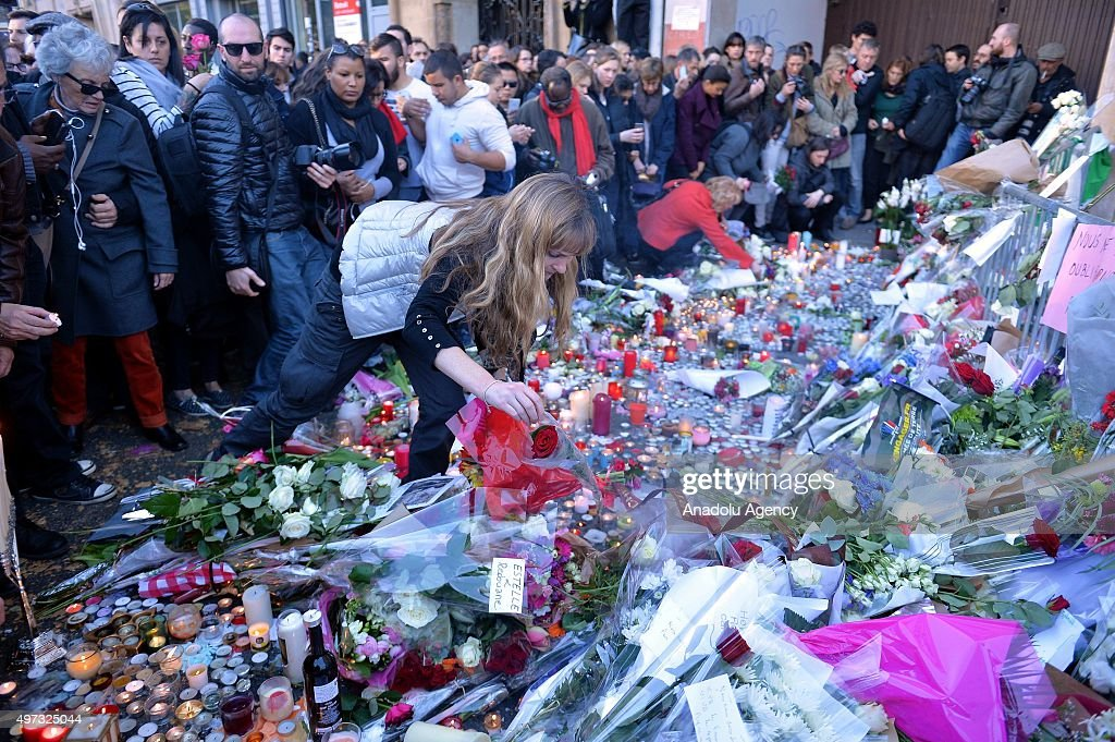 Members of the public gather to lay flowers and light candles in front of Bataclan concert hall following Friday terrorist attacks in Paris France on...