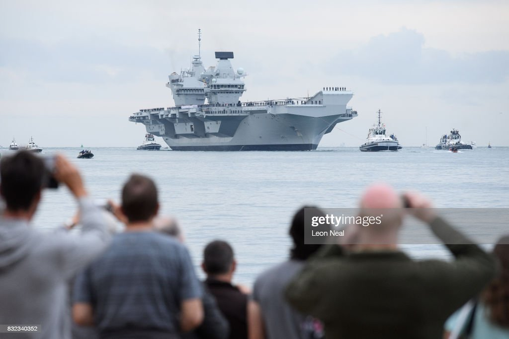 Members of the public gather to witness the arrival of the HMS Queen Elizabeth supercarrier as it heads into port on August 16, 2017 in Portsmouth, England. The HMS Queen Elizabeth is the lead ship in the new Queen Elizabeth class of supercarriers. Weighing in at 65,000 tonnes she is the largest war ship deployed by the British Royal Navy.