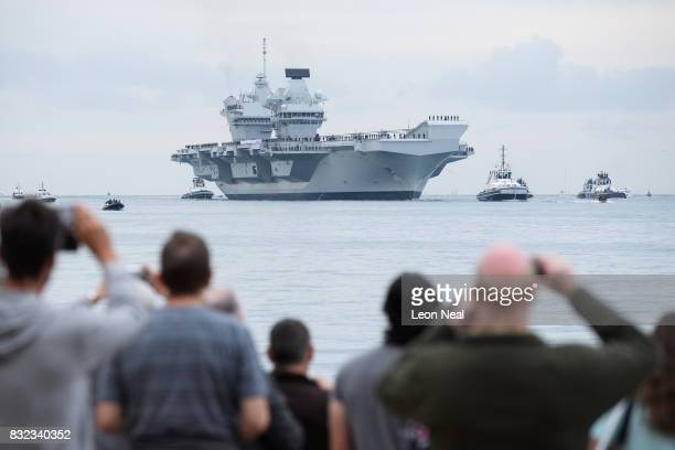 Members of the public gather to witness the arrival of the HMS Queen Elizabeth supercarrier as it heads into port on August 16 2017 in Portsmouth...