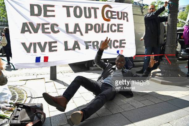 Members of the public hang a sign in support and solidarity with the police following an officer being shot yesterday on the Champs Elysees on April...