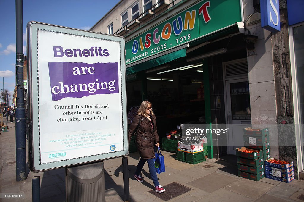 Members of the public in North London walk past a poster informing of changes to the benefits and tax system that have come into force yesterday, on April 2, 2013 in London, England. The widespread changes include a cut in housing benefit payments for working-age social housing tenants whose property is deemed larger than they need and council tax support payments being administered locally.