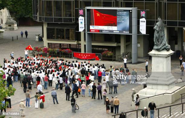Members of the public including a large number Chinese and Queen Victoria watch the opening ceremony of the Beijing Olympics on a giant screen in...