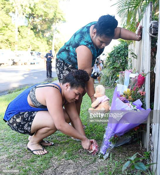 Members of the public lay a bunch of flowers across the road from the scene of a multiple stabbing in the suburb of Manoora on December 19 2014 in...