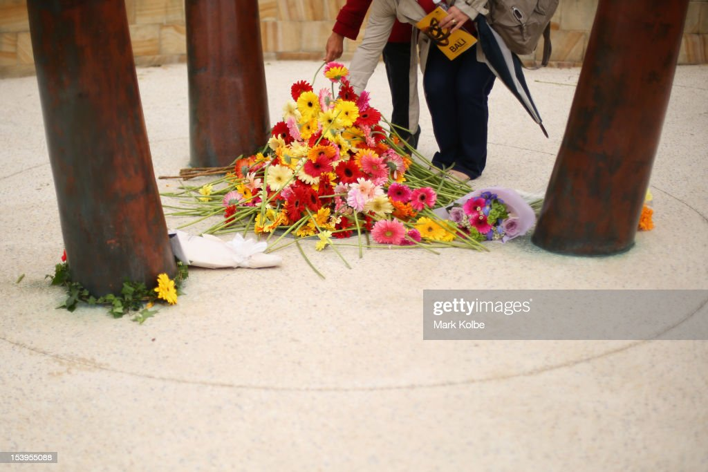 Members of the public lay flowers at a memorial ceremony at Dolphin Point in Coogee in on October 12, 2012 in Sydney, Australia. The ceremony marks tenth anniversary of the 2002 Bali suicide bombs that killed 202 people including 88 Australians.