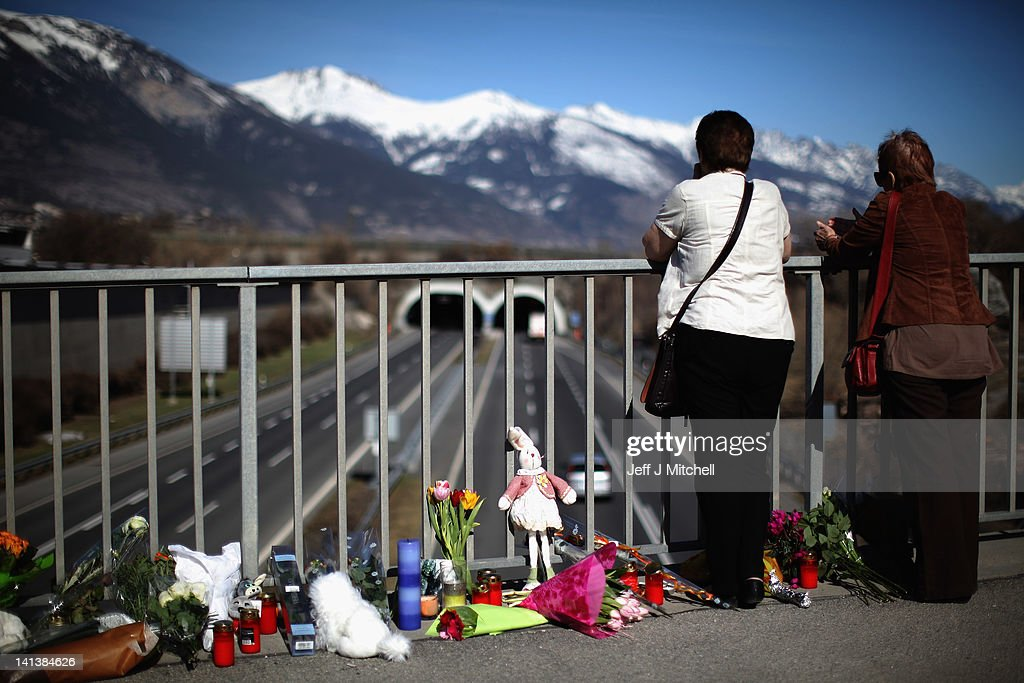 Members of the public lay flowers on a bridge near to the road tunnel where the 22 Belgian school children, four teachers and two drivers died in a coach crash, on March 15, 2012 in Sierre, Valais, Switzerland. The accident occurred on March 14, when a coach carrying 11-12 year old shcoolchildren returning from a skiing holiday crashed into a tunnel, killing 28 of the 52 passengers.