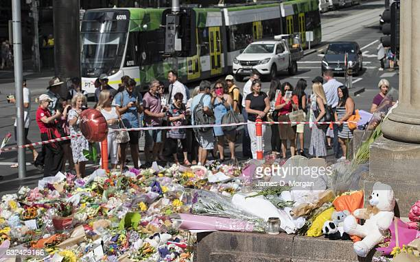Members of the public look at the flowers and messages of condolence as they lie on Bourke Street Mall on January 23 2017 in Melbourne Australia Five...