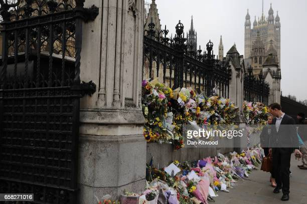 Members of the public look at the flowers left outside the Houses of Parliament in memory of those who died in last weeks Westminster terror attack...