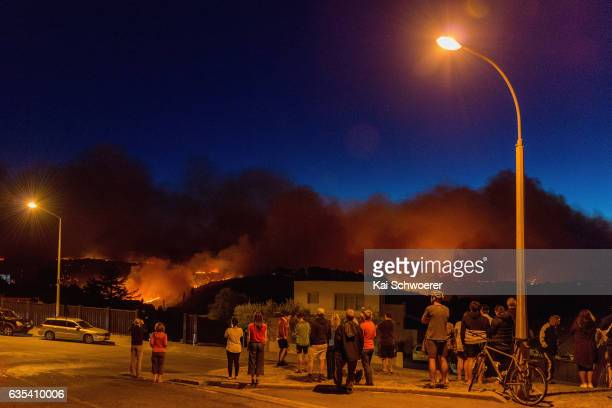 Members of the public look on as smoke and fire light up on February 15 2017 in Christchurch New Zealand A wind change has caused homes near the Port...
