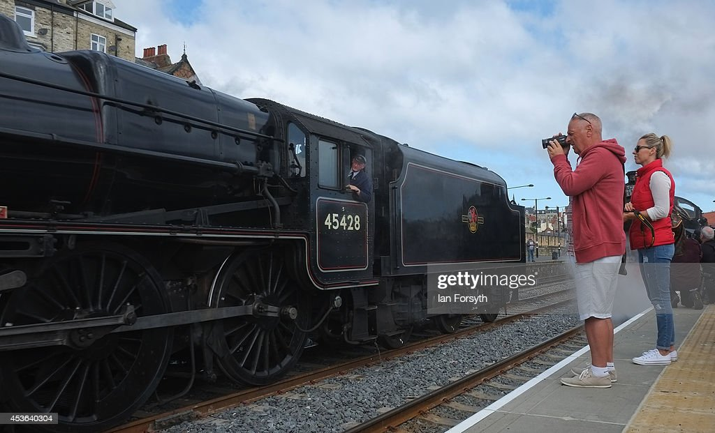 Members of the public look on at the steam locomotives, 'Chiru' and 'Eric Treacy' during an event to mark a second platform opening at Whitby train station on August 15, 2014 in Whitby, England. The second platform will provide passengers with more options for travel to the Yorkshire seaside town on the North Yorkshire Moors Railway and was the first time in half a century two steam locomotives were side by side at the station.