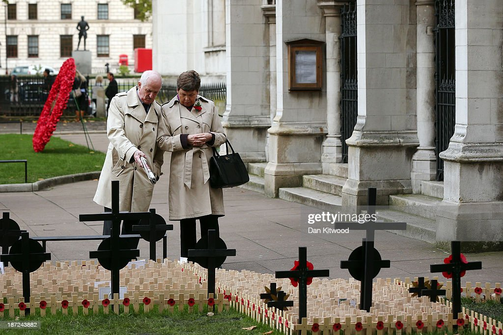 Members of the public look through remembrance crosses outside Westminster Abbey after the official opening of the Royal British Legion's Field of Remembrance on November 7, 2013 in London, England. Hundreds of small crosses bearing a poppy have been planted in the Field of Remembrance to pay tribute to British servicemen and women who have lost their lives in conflict.
