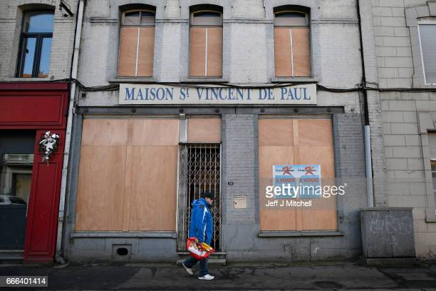 Members of the public make their way past boarded up premises on February 15 2017 in Henin Beaumont France The former mining town in northern France...
