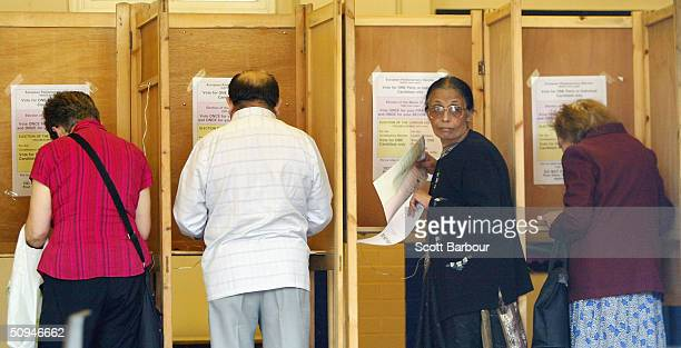 Members of the public mark their votes at a polling station on June 10 2004 in London England British voters are heading to the polls in the European...