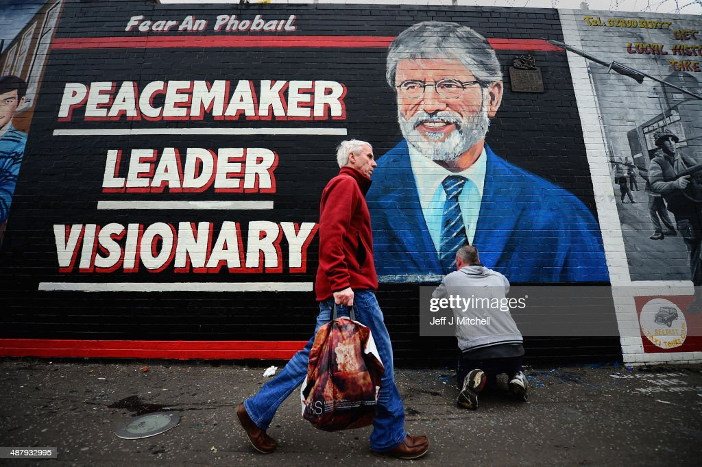 Members of the public pass a new mural of Sinn Fein Leader <a gi-track='captionPersonalityLinkClicked' href=/galleries/search?phrase=Gerry+Adams&family=editorial&specificpeople=203162 ng-click='$event.stopPropagation()'>Gerry Adams</a> painted on a wall on the Falls Road on May 3, 2014 in Belfast, Northern Ireland. The Sinn Fein leader has spent a third night in police custody in connection with the 1972 murder of mother-of-10 Jean McConville.