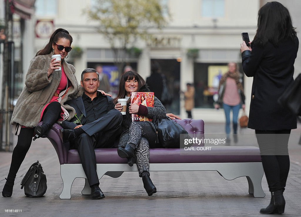 Members of the public pose for pictures with a waxwork model of US actor George Clooney during a photocall by London's Madame Tussauds to mark Valentines Day in central London, on February 13, 2013. AFP PHOTO/CARL COURT
