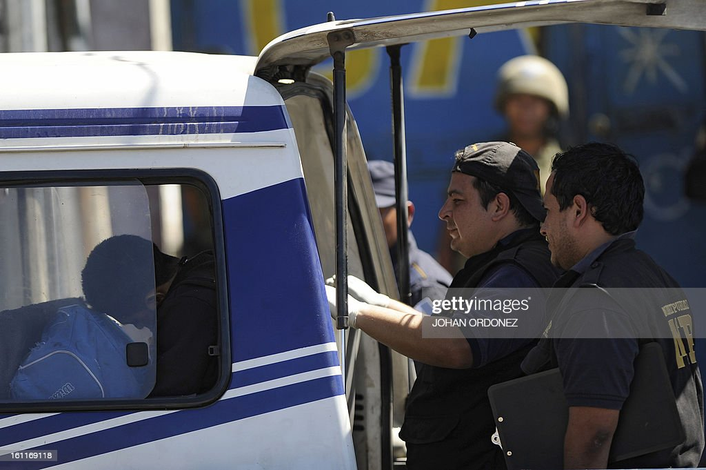 Members of the public prosecutor's office and police investigators inspect a van in downtown Guatemala City on Febrary 9, 2013. The vehicle was attacked by unidentified gunmen while traveling toward a prison; leaving two prison guards and a woman dead, authorities stated. AFP PHOTO/Johan ORDONEZ