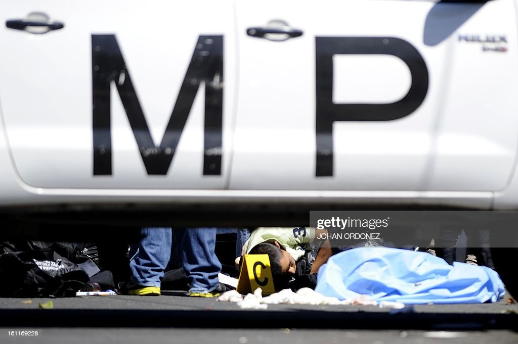 Members of the public prosecutor's office and police investigators inspect a crime scene next to a van in downtown Guatemala City on Febrary 9, 2013. The vehicle was attacked by unidentified gunmen while traveling toward a prison; leaving two prison guards and a woman dead, authorities stated. AFP PHOTO/Johan ORDONEZ