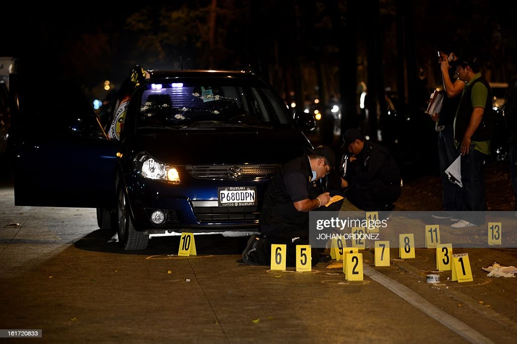 Members of the Public Prosecutors Office work at the crime scene where prominent Guatemalan lawyer, Lea De Leon Marroquin, was shot dead by unidentified gunmen in Guatemala City on Febrary 14, 2013. De Leon Marroquin had received threats after handling high-profile cases. AFP PHOTO/Johan ORDONEZ