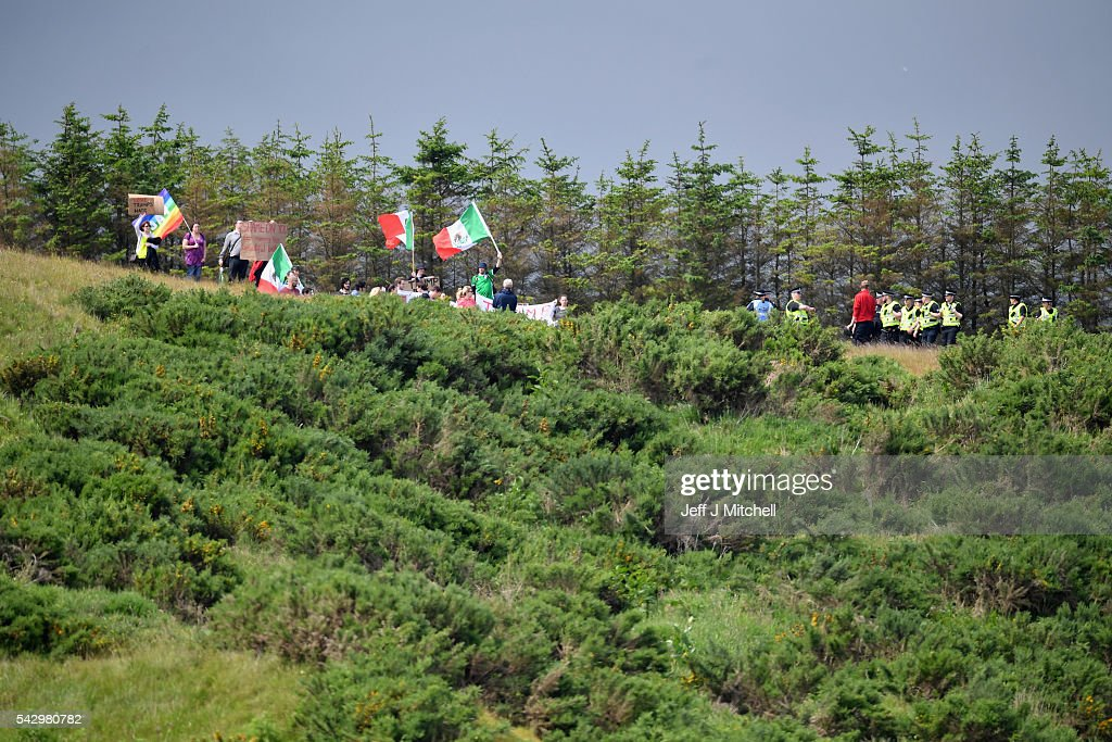 Members of the public protest as Presumptive Republican nominee for US president Donald Trump arrives at Trump International Golf Links on June 25, 2016 in Aberdeen, Scotland. The US presidential hopeful was in Scotland for the reopening of the refurbished Open venue golf resort Trump Turnberry which has undergone an eight month refurbishment as part of an investment thought to be worth in the region of two hundred million pounds.