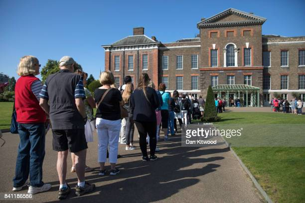 Members of the public queue to get into Kensington Palace where tributes continue to be left on the 20th anniversary of the death of Princess Diana...