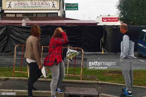 Members of the public react in front of the scene of a car crash into a pizza restaurant on August 15 2017 in SeptSorts 55km east of Paris which...