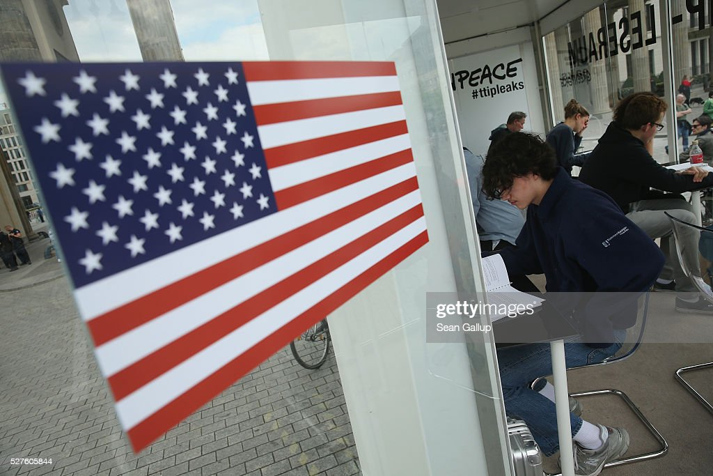 Members of the public read copies of documents detailing positions between U.S. and European negotiators over the TTIP trade agreement talks in a Greenpeace mobile reading room adorned with a U.S. flag on May 3, 2016 in Berlin, Germany. Greenpeace released the documents, which until then had been kept secret by U.S. and European governments, in a press conference yesterday. To many the released documents confirm widespread European fears that TTIP will undermine food safety, consumer rights and the legal system in Europe if implemented.