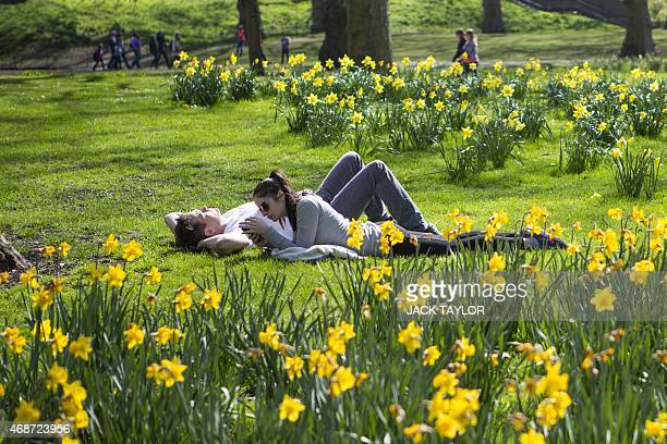 Members of the public relax in the sun in St James's Park central London on April 6 2015 as England basks in higher than expected temperatures on...