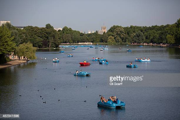 Members of the public relax on pedalos in the warm weather on Hyde Park's Serpentine lake on July 18 2014 in London England The Met Office has issued...