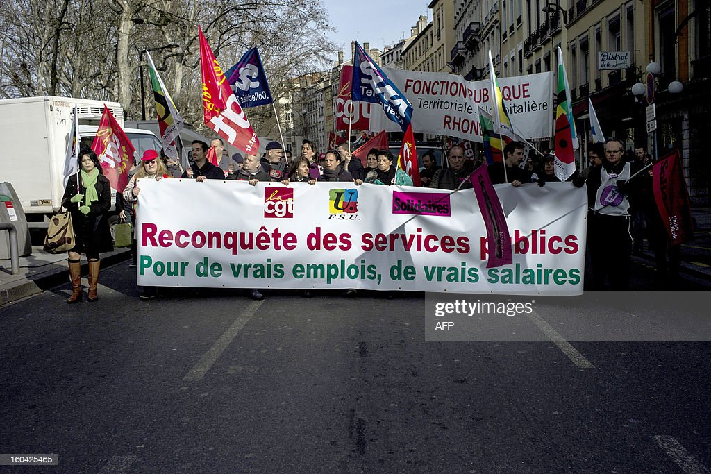 Members of the public sector, (education, health and finance) take part on January 31, 2013 in a national day of protest in Lyon against the French government's social policy. For the first time since French President Francois Hollande's election, three labour unions (CGT, FSU, Solidaires) called on 5.2 million civil servants to stop working to show to the government their unhappiness, particularly in terms of purchasing power. Banner reads 're-conquer of the public sectors. For real jobs, and real salaries.'