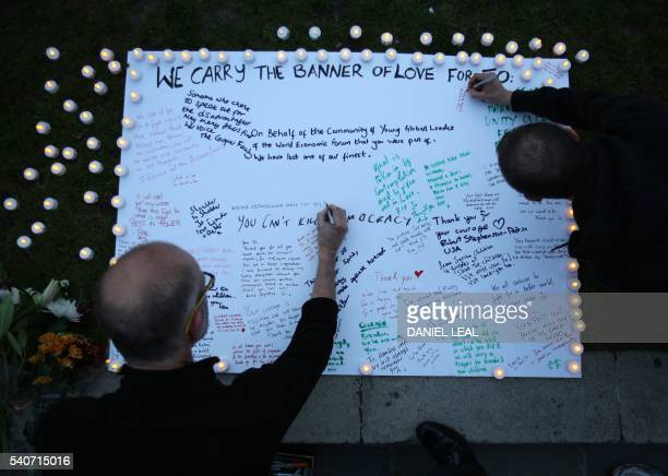Members of the public sign a white board of condolences at a vigil to slain Labour MP Jo Cox in Parliament square in London on June 16 2016 Cox died...