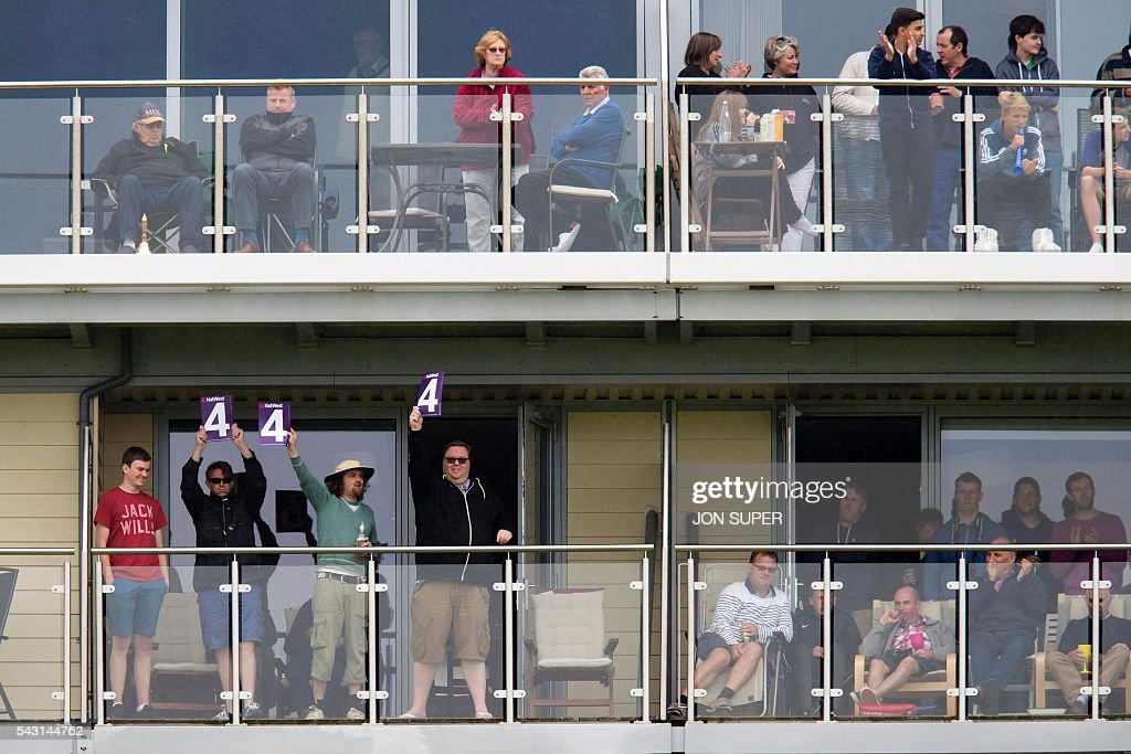 Members of the public signal a 4 as they watch the action from nearby apartments during the third one day international (ODI) cricket match between England and Sri Lanka at Bristol cricket ground in Bristol, south-west England, on June 26, 2016. Chris Woakes and Liam Plunkett both took three wickets apiece as England held Sri Lanka to 248 for nine in the third one-day international at Bristol on Sunday. / AFP / JON