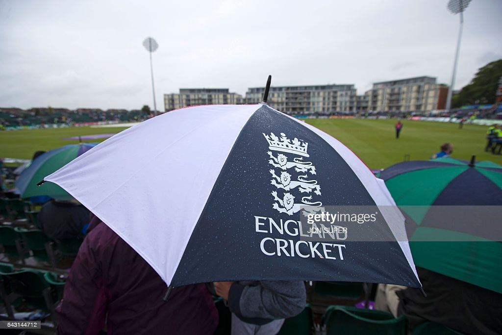Members of the public sit under umbrellas as rain stops play in the third one day international (ODI) cricket match between England and Sri Lanka at Bristol cricket ground in Bristol, south-west England, on June 26, 2016. Chris Woakes and Liam Plunkett both took three wickets apiece as England held Sri Lanka to 248 for nine in the third one-day international at Bristol on Sunday. / AFP / JON